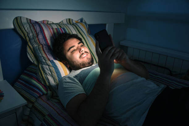 young man with his smartphone in bed - smartphone addiction not groups stock pictures, royalty-free photos & images