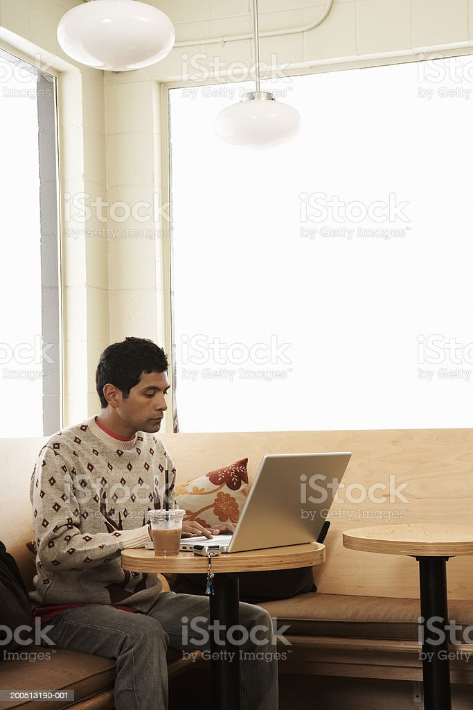 Young man with iced coffee using laptop in cafe royalty-free stock photo
