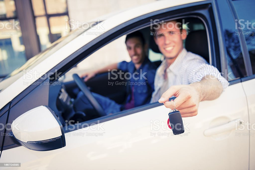 young man with keys of new , hire or rental car royalty-free stock photo
