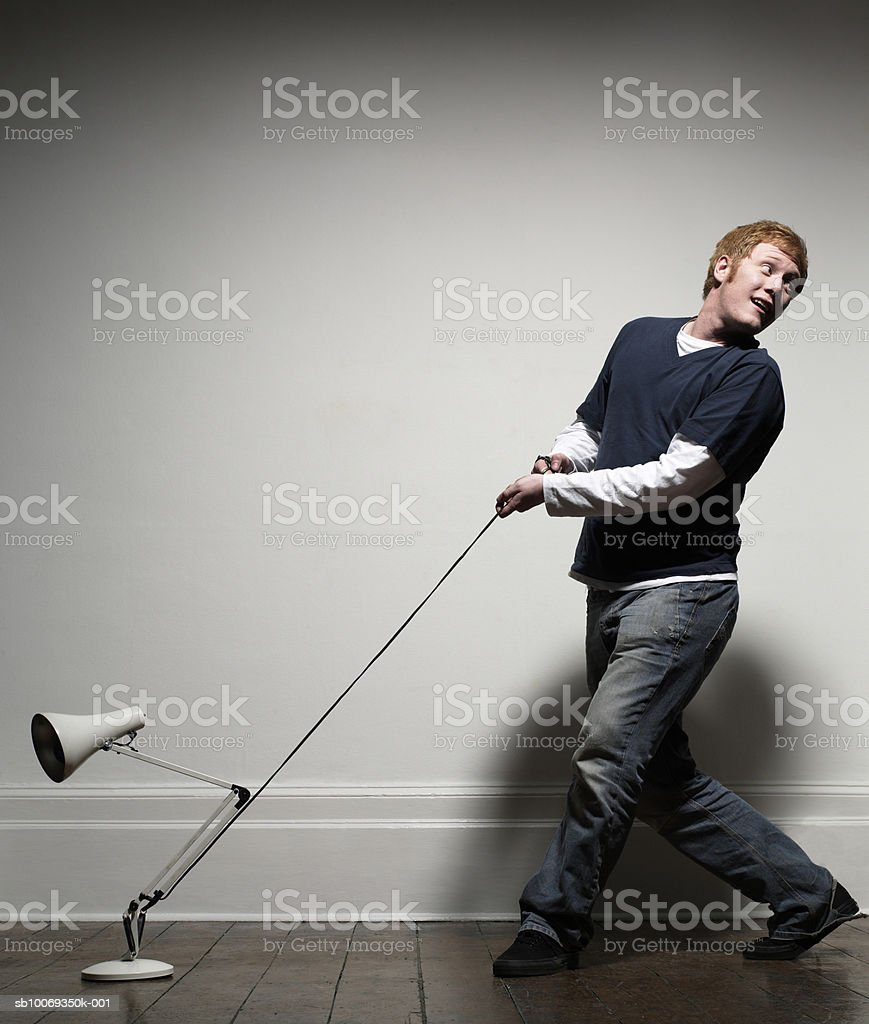 Young man with lamp on leash, indoors 免版稅 stock photo
