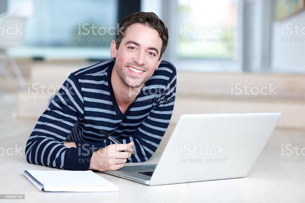 Young man with laptop on floor, smiling at camera royalty-free stock photo