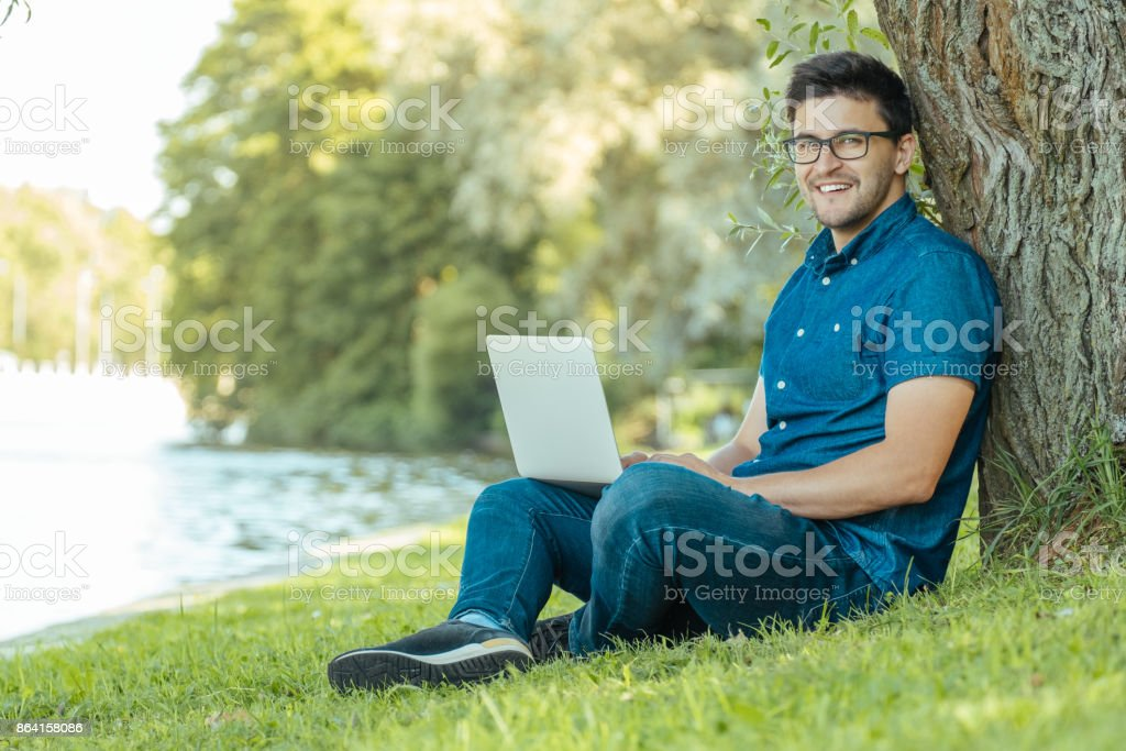Young man with laptop outdoor sitting on the grass. Remote working concept royalty-free stock photo