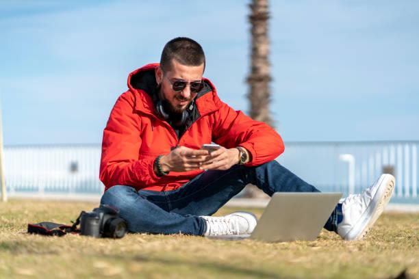 Junger Mann mit Laptop mit Smartphone im Sitzen auf Gras – Foto