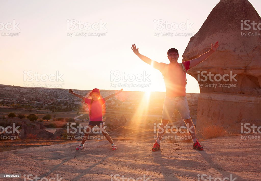 Young man with little daughter meeting sunset on mountain top stock photo