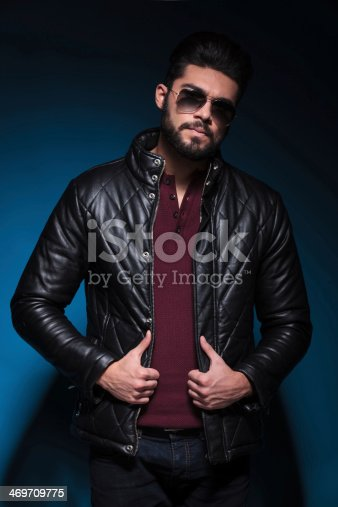 istock young man with long beard is holding his leather jacket 469709775