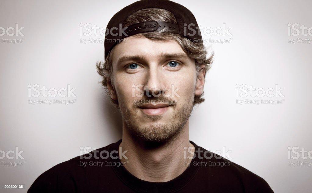 棒球帽上長卷髮的年輕人 - 免版稅一個人圖庫照片