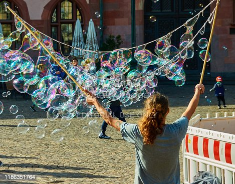 Frankfurt, Germany, October 2., 2019: Young man with long hair in blue shirt produced on the Roemer soap bubbles for the tourists to earn money