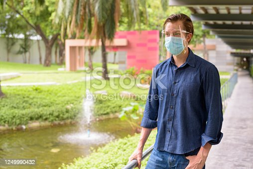 Portrait of young businessman wearing mask and face shield for protection from corona virus outbreak at the park outdoors