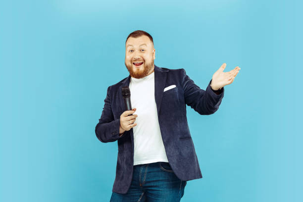 Young man with microphone on blue background, leading concept Young man with microphone on blue studio background, leading concept. Human emotions and facial expressions concepts. presenter stock pictures, royalty-free photos & images