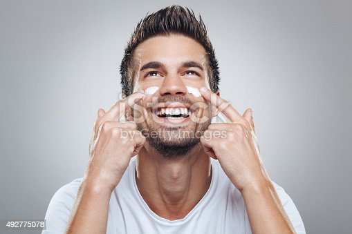 istock Young man with moisturizer on the face 492775078