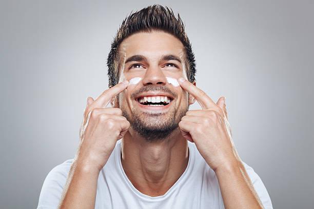 giovane uomo con crema idratante sul viso - prendersi cura del corpo foto e immagini stock