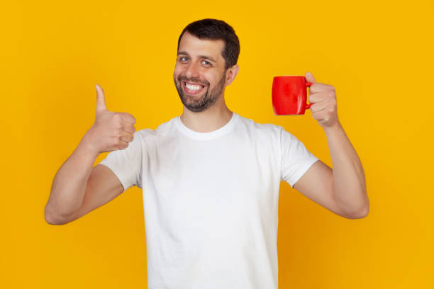 Young man with morning coffee mug in hand showing happy thumb up gesture stock photo