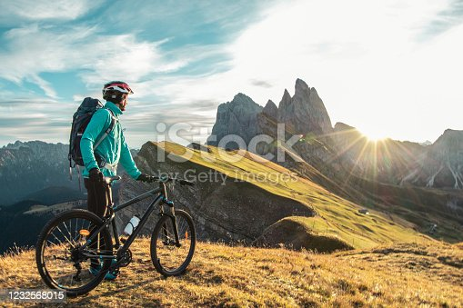 istock Young man with mountain bike on Seceda mountain peak at sunrise. Puez Odle, Trentino, Dolomites, Italy. 1232568015