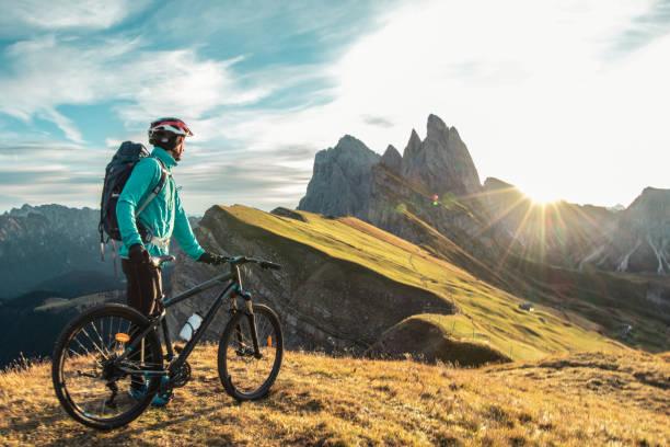 young man with mountain bike on seceda mountain peak at sunrise. puez odle, trentino, dolomites, italy. - dolomiti foto e immagini stock