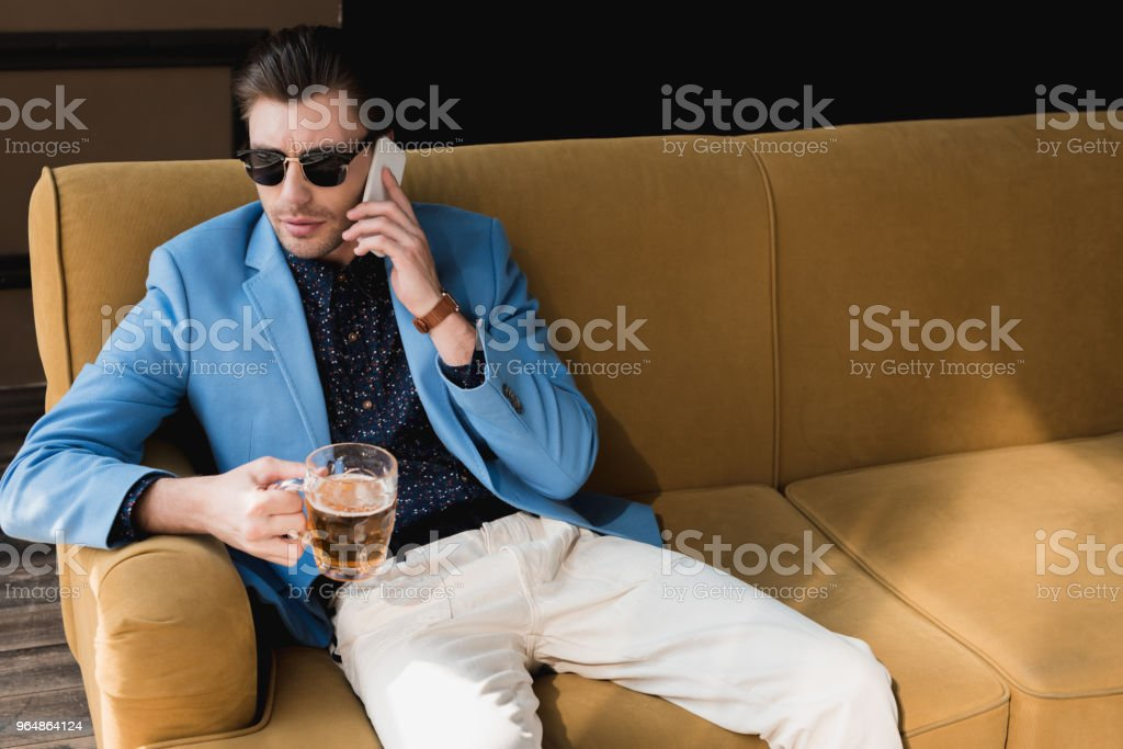 young man with mug of beer talking by phone while sitting on couch royalty-free stock photo