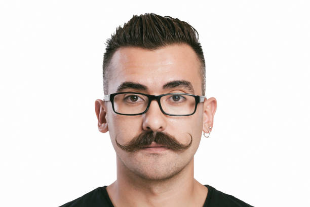 Young man with mustache Young male with glasses and mustache, white background, studio shot mustache stock pictures, royalty-free photos & images