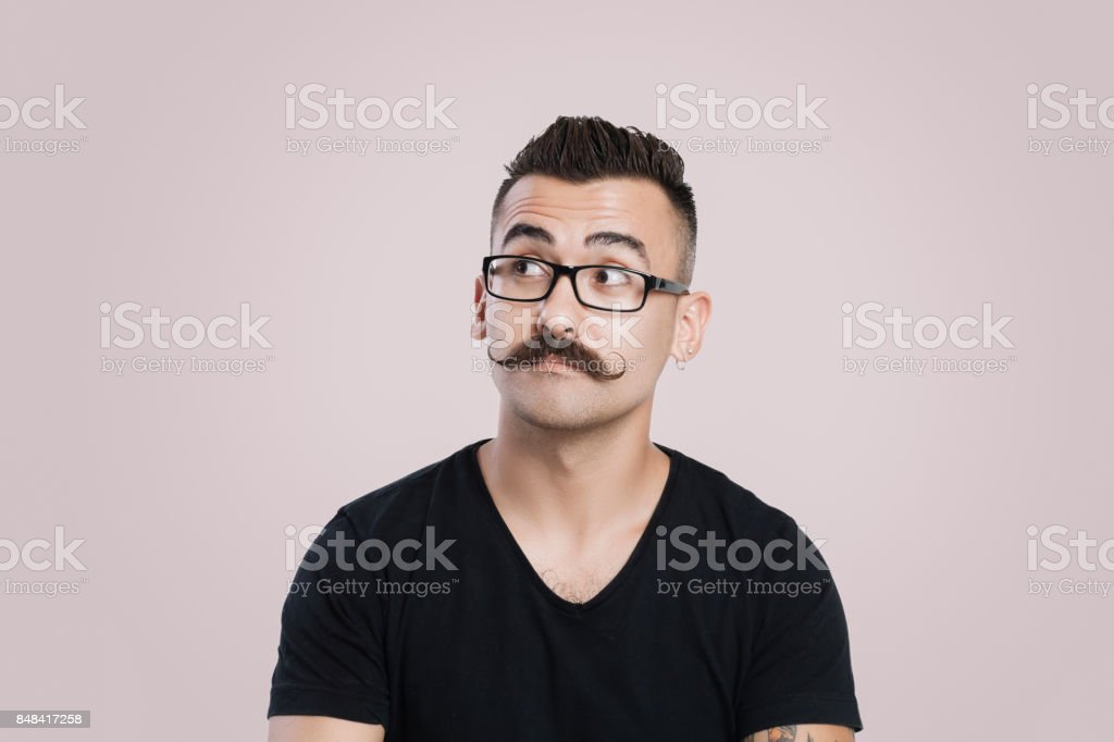 Young man with mustache, thinking and staring into space stock photo