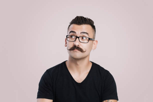 Young man with mustache, thinking and staring into space Young male with glasses and mustache, grey background, studio shot, raised eyebrow mustache stock pictures, royalty-free photos & images