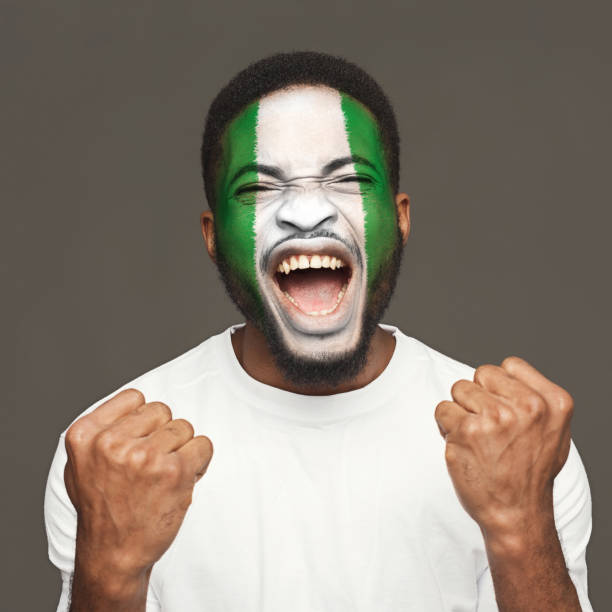 young man with nigeria flag painted on his face - soccer supporter portrait imagens e fotografias de stock