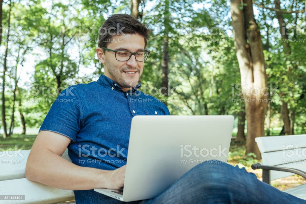 Young man with notebook sitting on the park bench royalty-free stock photo