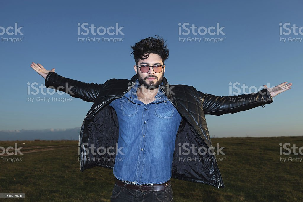 young man with open arms against blue sky stock photo