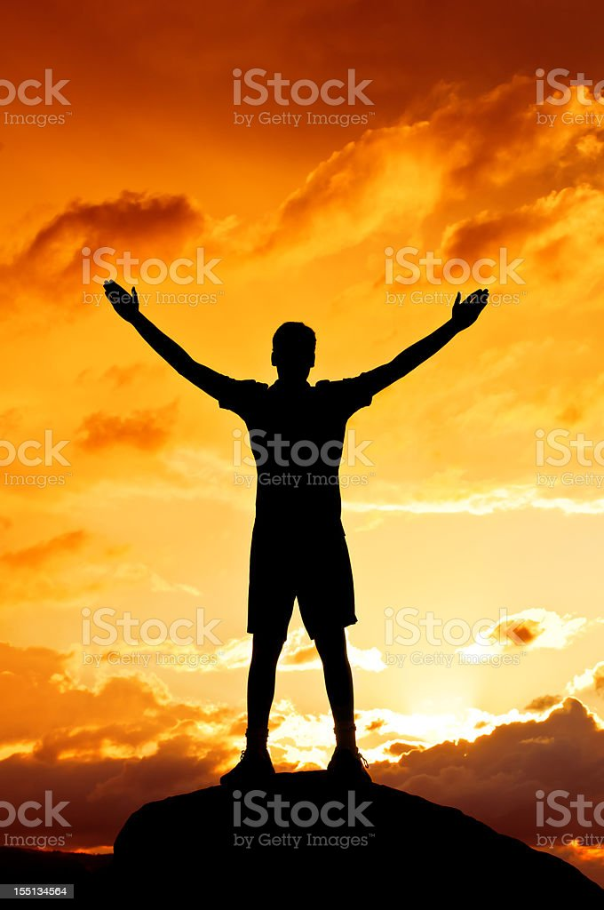 Young man with outstretched arms, sunset scenery after storm (I) stock photo