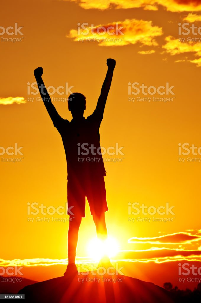 Young man with outstretched arms (sunset scenery) - V stock photo