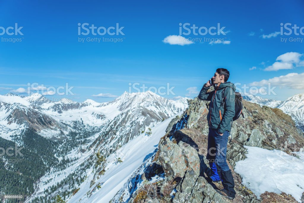 Young man with phone in hand on the top of a snowy mountain. Concept availability of mobile connection stock photo