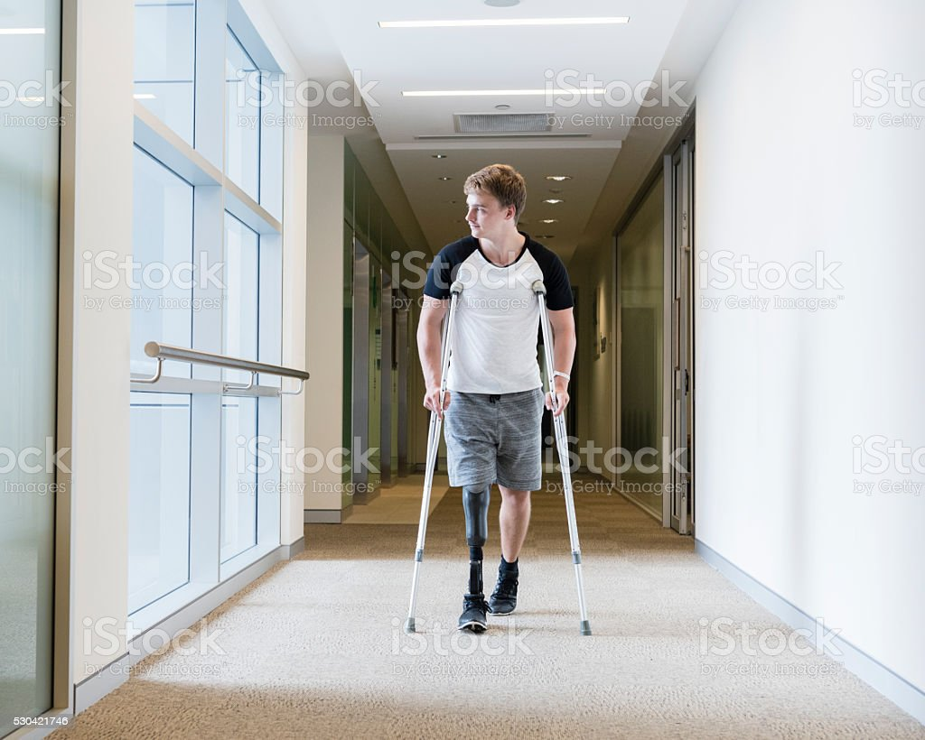 Young man with prosthetic leg on crutches stock photo