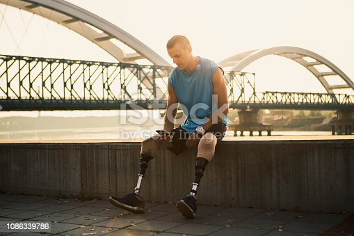 Young man with prosthetic leg seated outside taking break on his mobile phone