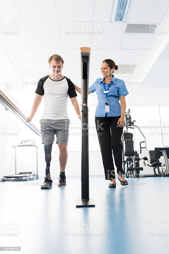 Young man with prosthetic leg using orthopedic equipment stock photo