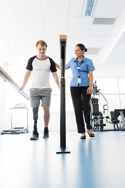 Young man with prosthetic leg using orthopedic equipment stock photo