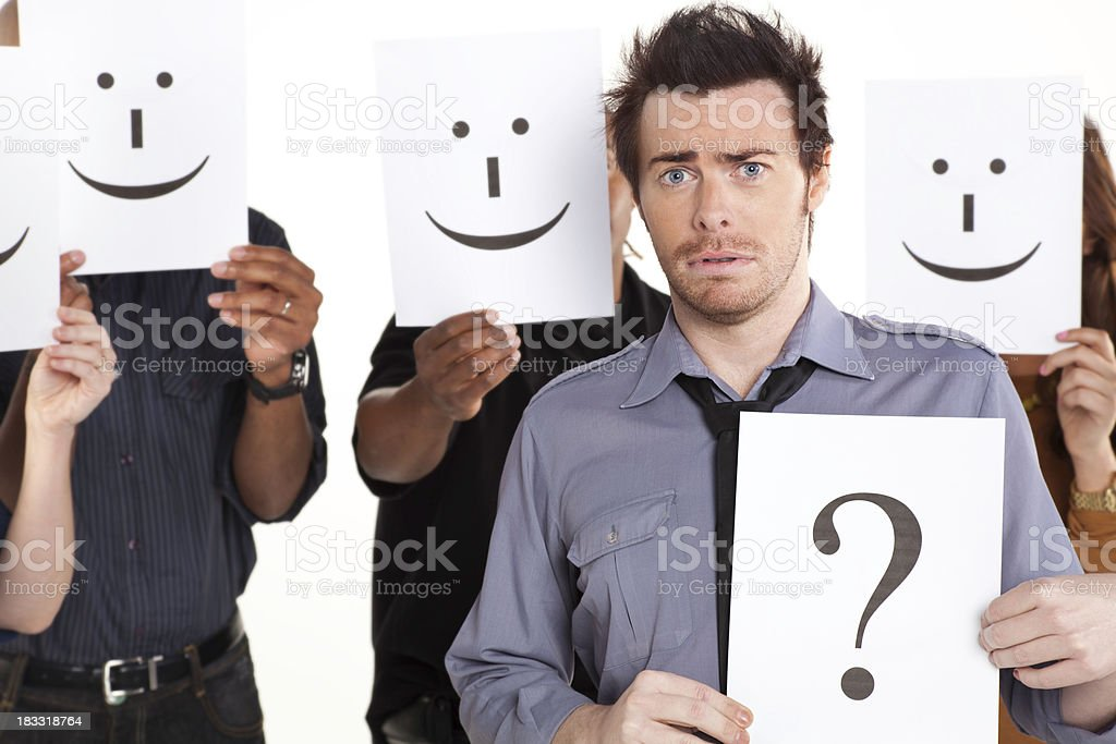 Young Man With Question Mark Sign Among Happy People royalty-free stock photo