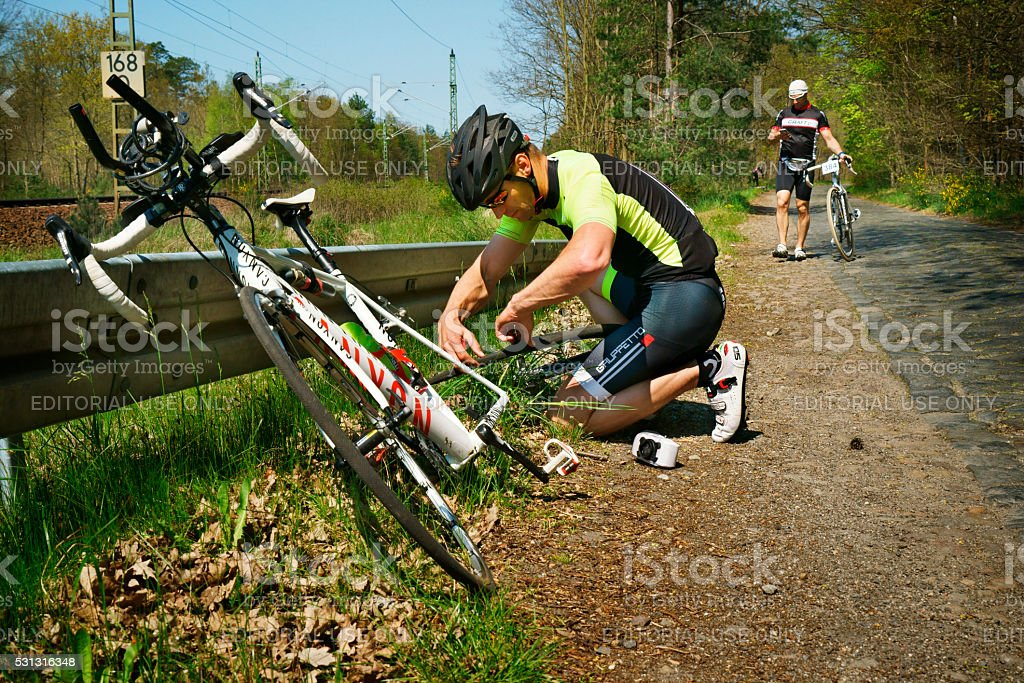 young man with racing bike repairing flat tire at roadside stock photo