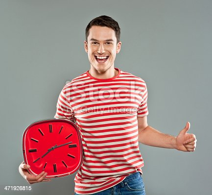 Portrait of happy young man wearing striped t-shirt, holding a big red clock and laughing at camera with thumb up. Studio shot, grey background.