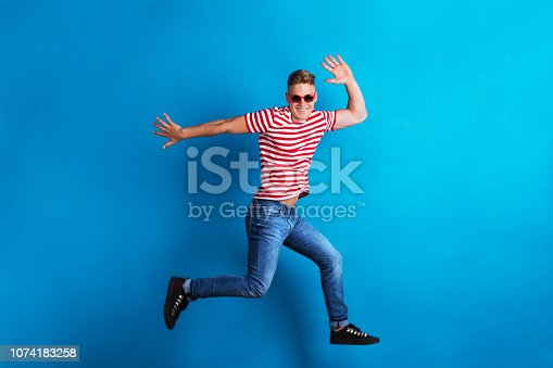 A young man with red sunglasses and striped T-shirt in a studio, jumping.