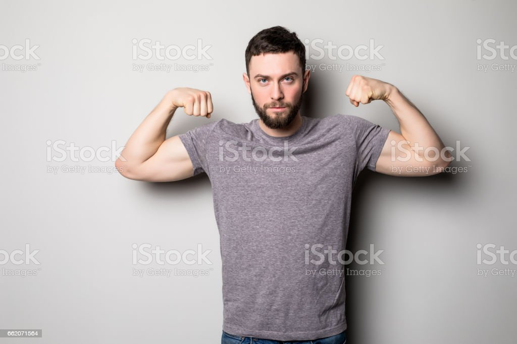 young man with relief muscles in jeans in shirt on a gray background royalty-free stock photo