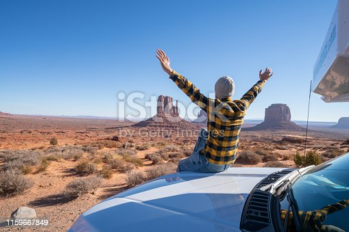 Road trip concept; Young man outside RV looking at landscape arms outstretched ; national parks and nature ready for adventure