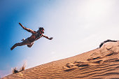 istock Young man with retro glasses doing parkour jump in desert 874098850