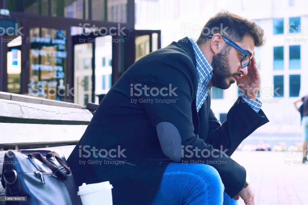 Young man with sad facial expression sitting on a bench in the park....