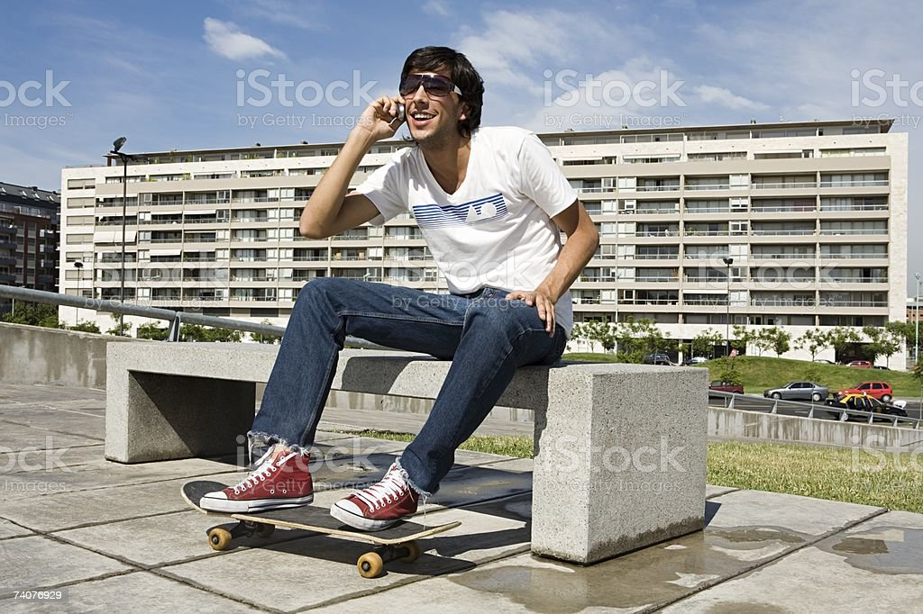 Young man with skateboard on cellphone foto de stock royalty-free