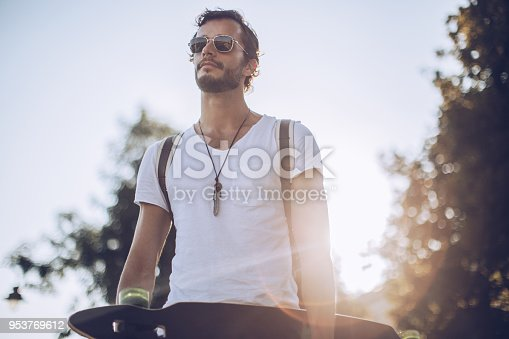 Young man with skateboard in park