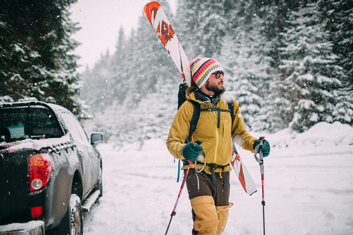 Young man with ski walking in the snow forest