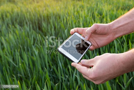 istock Young man with smart phone in field 1035073324