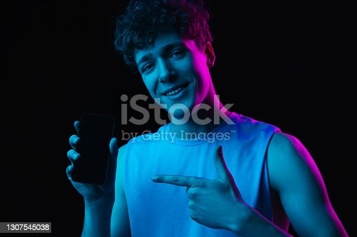 Pointing. Half-length portrait of young man with smartphone isolated on multicolored dark background in neon light. Concept of human emotions, facial expression, youth culture. Copy space for ad.