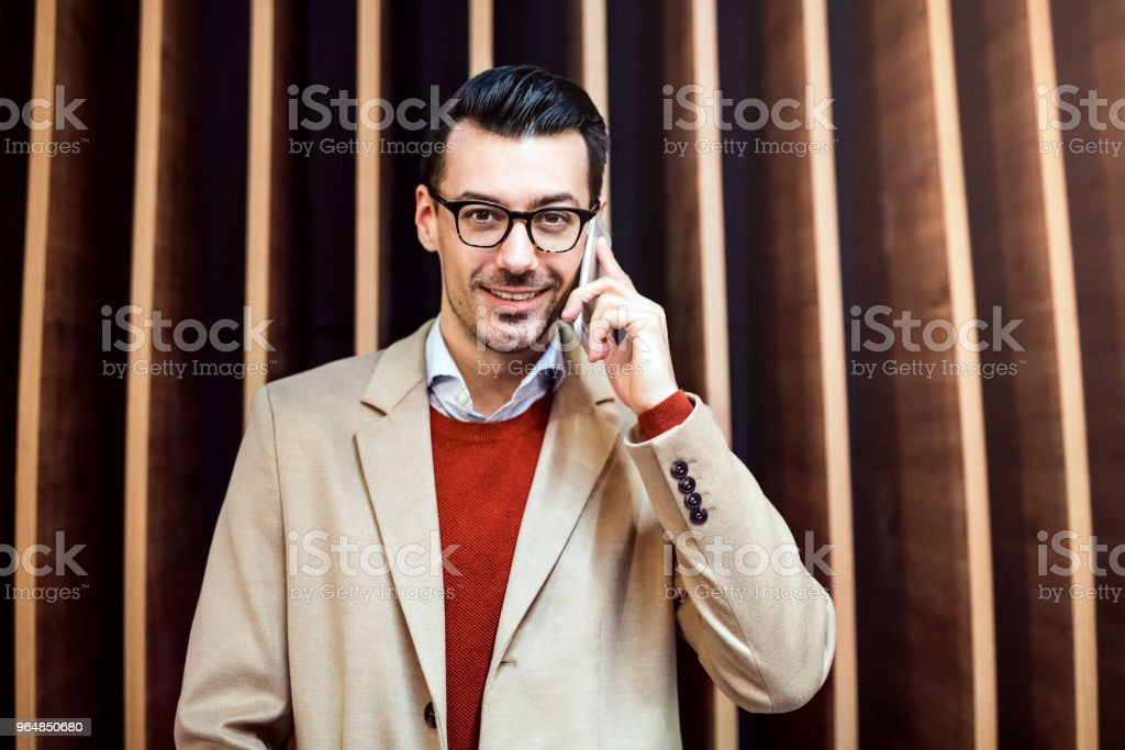 Young man with smartphone standing against wooden wall. royalty-free stock photo