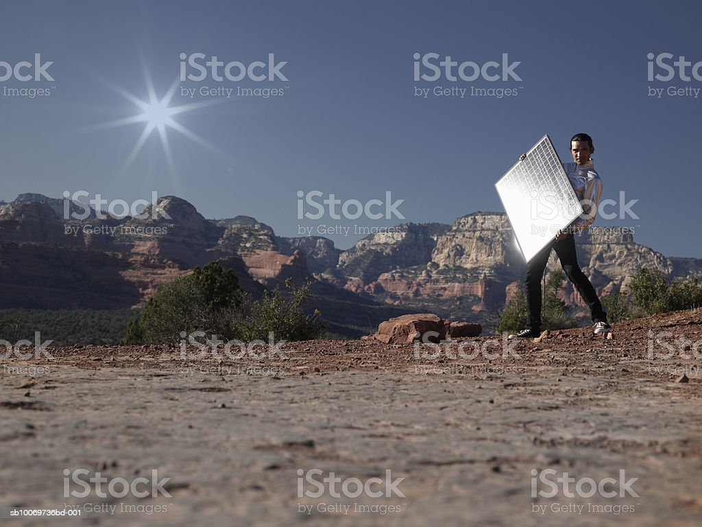 Young man with solar panel, side view royalty-free stock photo
