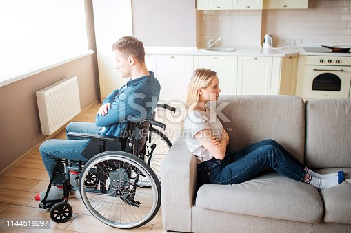 Young man with special needs and healthy woman sit back to back in room. Argue and quirrel. Worker with disability and inclusiveness. Upset and unhappy couple