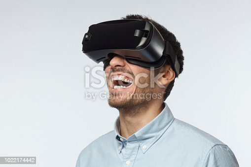1090878574istockphoto Young man with stubble wearing casual blue shirt, watching funny hillarious movie, using virtual reality 3d goggles, laughing 1022174442