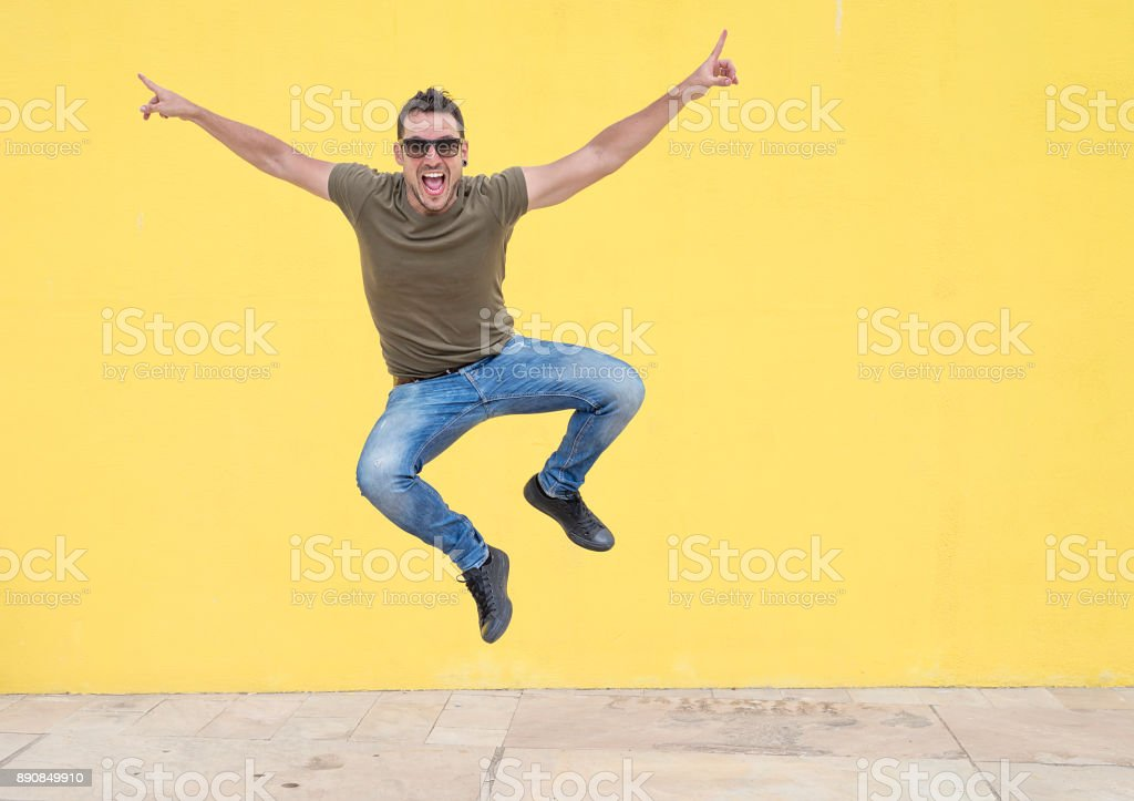 Young man with sunglasses jumping in front of a yellow wall. stock photo